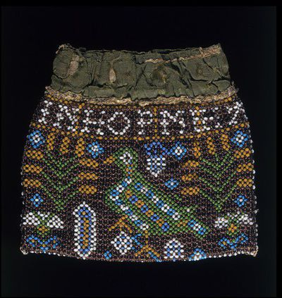 Bag of beads netted on linen thread, and silk linings, England, 1625-1650. Small flat bag of coloured beads netted on a foundation of thick linen thread, and patterned with bird and flowers and inscribed 'IN HOP ME HART DOTH REST'. With brown, green, white, yellow and blue beads. Lined with chamois leather. Above the beadwork is a band of material of green silk covered with a pale pink silk. There is also a pink satin lining and pink ribbon handles. The pink silk and satin are probably later additions.  Threaded linen and beads, lined with leather and silk.