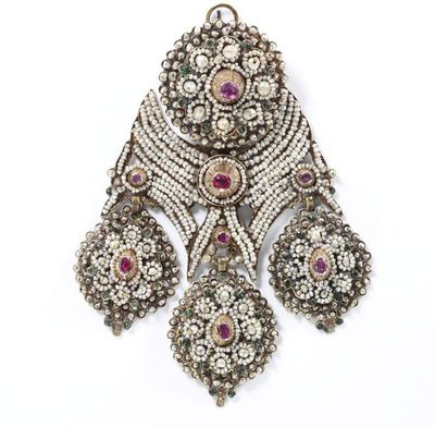 Gold girandole earring set with sapphires and green wax, and covered with seed pearls, Italy, 1800-1860.Girandole earring decorated all over with strings of seed pearls surrounding high conical mounts set with pink sapphires over red foil, and small pastes of green wax, imitating emeralds. Hinged wire at back, with loop at top.Gold set with foiled pink sapphires and green wax, covered with strings of seed pearls.