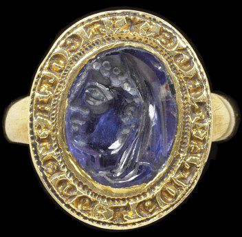 Gold signet set with a sapphire intaglio of a woman's head. Inscribed around the bezel :'*TECTA: LEGE: LECTA: TEGE'. Possibly set in England, 1275-1325.Signet ring, gold, set with a sapphire. Around the oval bezel is engraved in Latin in Lombardic lettering '* TECTA: LEGE: LECTA; TEGE'. The hoop of the ring is open at the back of the bezel so that the finger can touch the sapphire. The sapphire intaglio in the centre of the bezel is engraved with a head in profile of a lady in a veil.Gold, engraved; sapphire, carved.