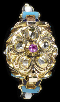 Enamelled gold ring with an oval bezel, a hinged cover set with a pink sapphire in a border of rose-cut diamonds, below a compass dial, with volutes and strapwork on the shoulders, possibly made in Germany, 1850-1900.Enamelled gold ring with an oval bezel, a hinged cover set with a ruby in a border of rose-cut diamonds, below a compass dial, with volutes and strapwork on the shoulders.Enamelled gold with a pink sapphire and rose-cut diamonds.