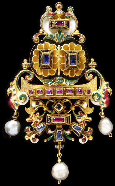 Pendant-brooch, gold, enamel, set with rubies, sapphires and pearls, Castellani, Rome, 1860-1900.Enamelled gold pendant-brooch: above a curved central line of seven rubies mounted in rectangular collets are two gold rosettes centred by sapphires beneath, at the top, ruby mounted in a collet in a heart-shaped frame. Beneath the line of seven rubies a symmetrical design of enamelled openwork gold, a central ruby beneath one sapphire and above three others. Pendent pearls hang beneath the profile head of a bird on either side of the line of rubies and from the bottom of the pendant-brooch. Gold back engraved with reserves which are matted. Two of Castellani's monogram plaques are incorporated into the design.Gold, enamel, set with rubies, sapphires and pearls.
