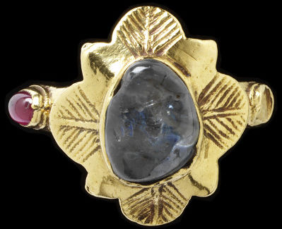 Gold ring with flower-shaped bezel set with a sapphire. The shoulders have settings for stones, one holding a garnet, the other empty, Western Europe, 1300-1400.Gold ring, the chased flower-shaped bezel set with a sapphire. The shoulders having settings for stones, one holding a garnet, the other empty.Gold set with a sapphire and garnet.