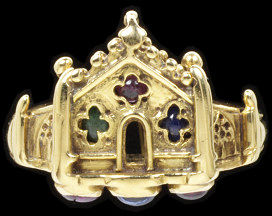 Gold ring, with a bezel in the form of a facade of a church, set with an amethyst, an emerald and a sapphire, with a sapphire flanked by rubies below, designed by W R Lethaby and made by Henry Wilson, London, 1901.Gold ring, with a bezel in the form of a facade of a church, set with an amethyst, an emerald and a sapphire, with a sapphire flanked by rubies below, the hoop struck with Henry Wilson's monogram.Gold with an amethyst, emerald, sapphires and rubies.