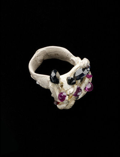 Ring of silver set with blue and pink sapphires and other gems, made by Karl Fritsch while teaching a masterclass at the RCA 2002-3. Round hoop with irregular outline, the wide bezel randomly scattered with faceted gemstones.Silver, blue and pink sapphires with other gems.