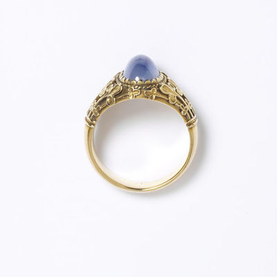 Gold ring set with a cabochon sapphire, designed by William Burges, made by an unknown goldsmith, England, ca.1870.Gold ring, the oval bezel set with a cabachon sapphire in a serrated collet with applied stiff leaf ornament on the shoulders.Gold set with a cabochon sapphire in a serrated collet and with applied ornament.