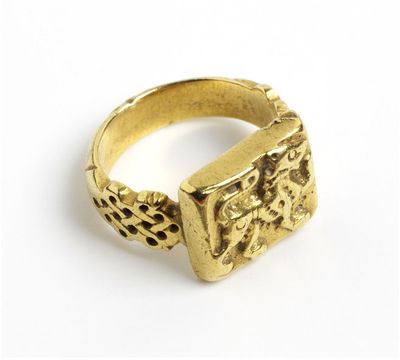 Gold ring, with a lion passant, Sicily, 12th century.Ring, gold, cast and chased. The shaped shoulders of the decorated with an interlace pattern. The flat rectangular bezel set with a high relief lion passant, with incised detailing.Gold, cast and chased.