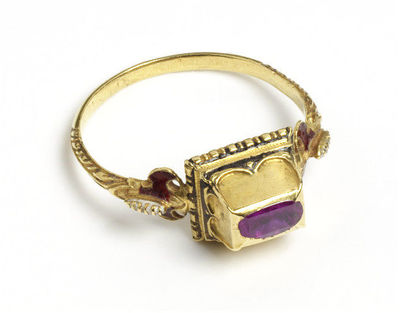Enamelled gold ring, oblong box bezel set with a table-cut pink sapphire, with shaped shoulders, Western Europe, 1550-1600.Ring, gold, enamelled and set with a pink sapphire. The plain hoop with winged shoulders supporting an oblong box bezel chased with double arches and set on a reeded cushion-like base with beaded edge. The bezel is set with a foiled table-cut pink sapphire in a rubbed-over setting. The winged shoulders are enamelled in translucent red and white and bear traces of black enamel. The base of the bezel and the quatrefoil petals retain traces of black enamel.Gold, cast; enamel, pink sapphire.