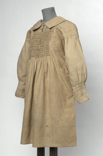 Boy's rural smock of beige drabbet, made in England, 1860-1869. Hand-sewn 'round frock' smock of light brown drabbet. The collar and shoulder-straps are embroidered with a simple meandering line, and the box with stylized designs of plants and insects. The gathering, the sleeve tops, and the cuffs are all smocked in feather and bar stitches. There are two side pockets, the lid of each fastening with a button and a stitched buttonhole. The neck fastens at the front with a hook and bar, which are modern additions.  Hand stitched and embroidered drabbet.