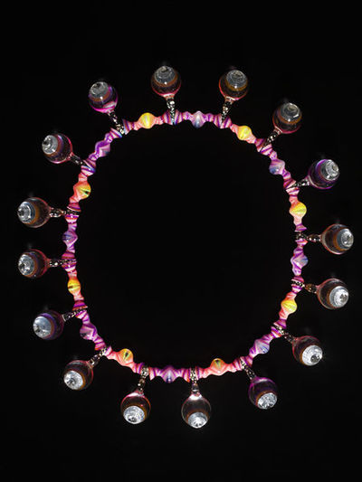 Necklace, acrylic, by Adam Paxon, England, ca. 2004.Large necklace of psychedelic acrylic beads hung at regular intervals with sixteen globular drops. The beads, striped pink and purple, have a long undulating shape and swell towards the middle with alternate centres of yellow and blue. The drops, which at the front are pointed and have reflective panels inset, are mostly of clear acrylic but at certain angles are suffused with colour from a thin layer of pink, orange or purple acrylic towards the front. Where the drops extend upwards to join the necklace the acrylic darkens and is decorated with green spots. A white spot on the back of one of the drops marks the top of the necklace which would be at the back of the neck when worn.Acrylic sheet, thermoformed, laminated and carved.
