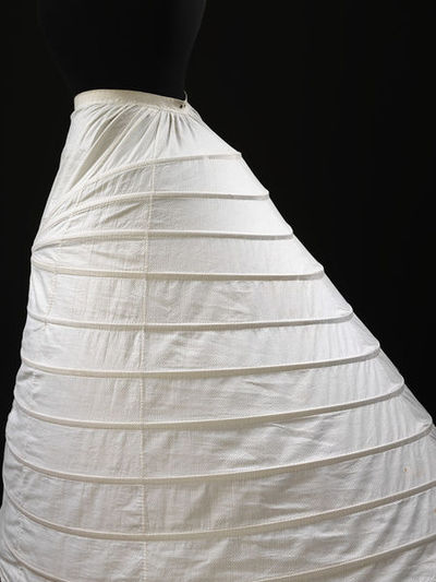 Crinoline frame, spring steel covered with cotton, England, 1858.Crinoline frame of white cotton with an all-over self-coloured woven spot pattern and covered spring steel frame. It is approximately mid calf-length and is shaped by the insertion of woven cotton covered metal steel inserted through tapes. Elasticated waistband and button fastening down centre front. It fastens at the waist with two brass metal hooks and eyes and down the centre front with small two hole white ceramic buttons. There are two brass metal punched eyelets at the centre back waist-band and a tape attached from here to each side of the back holds the shape. It is hand stitched.Spring steel frame covered with cotton.