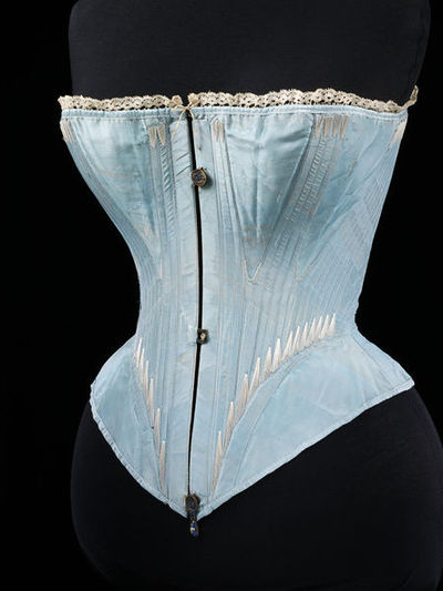 Boned corset of silk trimmed with machine-made lace, possibly made in France or Great Britain, 1864.Corset of blue silk trimmed at the top edge with a narrow band of machine-made lace. The corset reaches the top of the hips and is gored at the bust and hips. The corset is stiffened with whalebone and machine-stitched with an incised swivel latch to lock the busk fastening. There is a lace fastening at the back. Boned at the centre front, back and diagonally from the side to back and sides to front. The boning is hand-stitched into place. Metal eyelets. Lined with cotton twill.Silk, edged with machine-made lace, reinforced with whalebone, metal, lined with cotton twill.