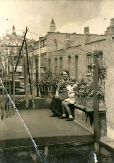 Black and white portrait photograph of a young girl, Lottie and her grandmother posing on a rooftop of their home in Bethnal Green, ca. 1900.  Black and white photograph of a young girl and an older woman sitting in the flat roof of a house in the city. They are sitting amongst some potted plants. Terrace houses and a church can be seen in the background. Black and white photograph.