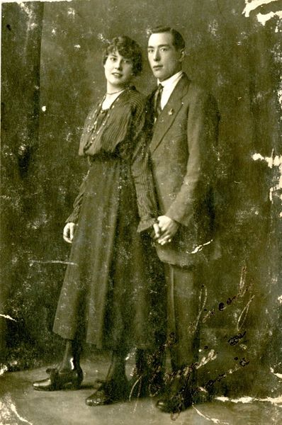 Black and white portrait photograph of Frederick Longcroft (Jim) posed with Em ca. 1900.  Black and white photograph of a brother and a sister posed standing up and holding hands. The male is wearing a smart suit with a white shirt and tie. The girl is wearing a long skirt and blouse. Black and white photographic postcard.