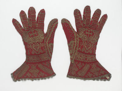 Ecclesiastical glove, Spanish, 16th century. These gloves are knitted from red silk yarn and yellow silk partially wrapped with silver strip in stocking stitch. Made for a bishop, they are decorated geometric designs and a cross. There are 23 stitches/20 rows per inch. The gloves are embellished with silver-gilt bobbin lace.  Silk and silver strip, hand knitted.