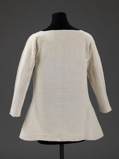 Jacket for an adult, knitted in white cotton, English, 18th century. A long sleeved jacket of white with a pattern of chevrons along the lower edge, the front edges, the centre back and the inner and outer sleeve, made up of knit, purl and moss stitches. The waist is shaped with gores made by decreases. The back and front are knit in one piece, dividing at the sleeves and knit together at the shoulders. The sleeves are made from stitches from the main body and picked up from the front and back and knit to the wrist. The front edges are bound with a 6mm wide strip of linen.  Hand knit with two-ply white cotton yarn.