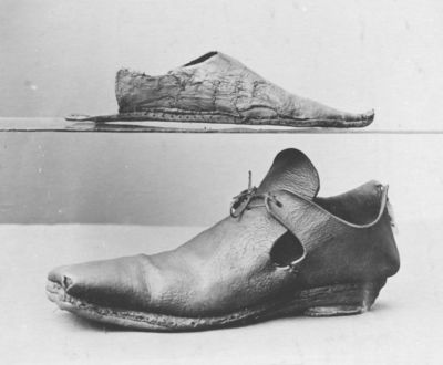 Left leather shoe with long pointed toe but missing quarters, London, late 14th century. Left leather shoe with long pointed toe (poulaine). Vamp shaped into a point at throat. Quarters missing.  Tanned leather (modern thread and textile).