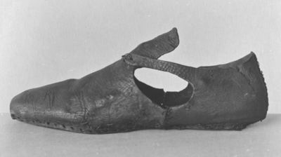 Left shoe of leather with round toe and open side, remains of latchet fastening over tongue, London, ca. 1600. Left shoe of leather with round toe and open side. Only one latchet (left side) is remaining, originally tied over tongue (parts missing).  Tanned leather (modern thread).