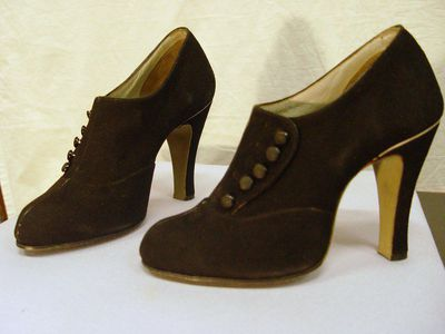 Pair of ladies' suede shoes, Regent Shoe Store, London, England, ca. 1938-1939. Pair of ladies' shoes made from black suede, the centre front seam faced with black patent leather and the heel with white. The buttons on the high, side fastening upper are black with the flat tops matte finished. The shoes are lined with grey leather and have a heel grip. Stamped in gold on the sole is 'MADE IN BELGIUM ESPECIALLY FOR REGENT SHOE STORE, 31 WARDOUR STREET, SHAFTESBURY AVENUE, LONDON, W1.' Incised in beige stained sole is 'EXCLUSIVE 10cm HEEL MADE IN BELGIUM'. On the side of the white, paper covered box is 'R Bik Suede Button Shoe No.9 10cm 37 37.'Suede, patent leather.