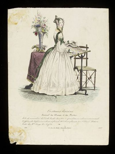 Woman standing at an embroidery frame by Lesage, with a Taglioni hairstyle (dressed by Mme Perrot). Hand-coloured engraving from the Journal des Dames et des Modes, 1836. Woman in an interior. She stands at an embroidery frame in a white dress with dark green satin sash and decorative shoulder braces. Also in the scene is a table covered with a maroon cloth with a large vase of wildflowers and a basket of embroidery silks, and a chair with a caned seat.