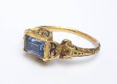 Enamelled gold ring with a table-cut sapphire in a 4-petal bezel setting, the shoulders with volutes, Western Europe, c. 1525-1575.Ring, gold, enamelled, set with a sapphire. The rectangular 4-petal bezel set with a table-cut sapphire, the shoulders with volutes. Traces of enamel on the bezel and the shoulders.Gold, enamel, sapphire.
