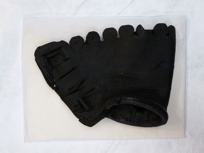 Leather gauntlet decorated with rectangular tabs and circular cut outs.  Tanned leather
