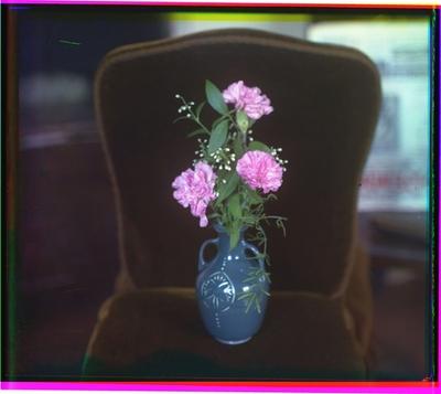 Blomster i en vase på en stol.