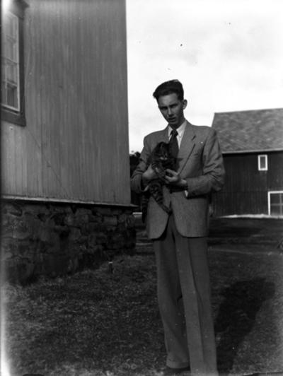 Ung mann som holder en katt.