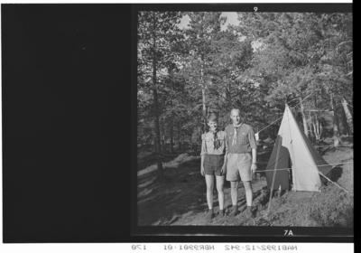 Speider og leder utenfor et telt. Furuskog.