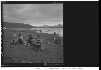 Tre speidere sitter ved et bål i fjæra, to leser aviser. Fjord og landskap i bakgrunnen.