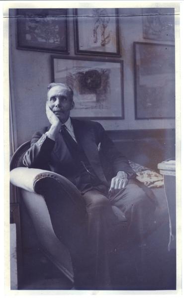 Portrett. Johan Berner Jakobsen sitter på en sofa. På veggen henger innrammet grafikk.