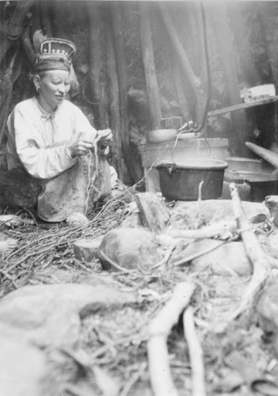 Skoltesamekvinnen Tatjana Fesdolova Titoff inne i gammen ved laksefiskeplassen ca 1900