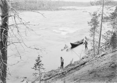 To menn trekker elvebåten oppover Grensefoss, Pasvik