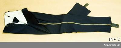 Långbyxor m/1895, Långbyxor m/1895, för Skånska husarregementet : Mörkblått kläde, guldgalon m/1895 längs yttersömmarna, två sidofickor. Svarta läderhällor att knäppas under foten med mässingknappar. Foder av vitt siden.