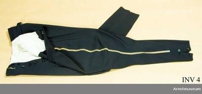 Ridbyxor m/1895, Ridbyxor m/1895 för Skånska husarregementet : Mörkblått kläde, guldgalon m/1895 längs yttersömmarna, två sidofickor och en bakficka. Byxbenen slutar strax under vaden, där de knäpps med två bakelitknappar. Foder av vitt siden. Har för ridbyxor så kallad vid tillskärning.
