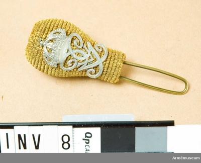 Pompong m/1895, Pompong m/1895 till husarmössa för Skånska husarregementet : Officer, Skånska husarreg. Överspunnen med guldtråd. Försedd med G VI A:s namnchiffer. Hål för ståndare.