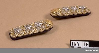 Axelklaffar m/1899-1931, Axelklaff m/1899-1931 till vapenrock m/1845 för General vid Generalitetet. : 3 flätade beläggningssnören av guldtråd. Förgylld mässingsknapp samt 3 försilvrade stjärnor för general. Foder av mörkblått kläde.