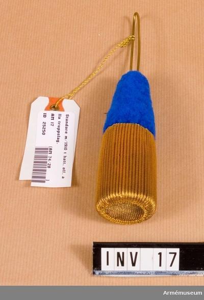 Ståndare m/1910,  : I blått och guld . En smalare del av blått ullgarn och en övre, bredare del i gulddragararbete (spunnen guldtråd). Fäste likt en ögla av mässing. 1978 inventerad.