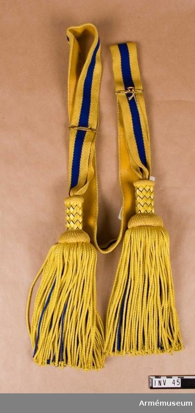 Paradskärp m/1819-29, Paradskärp m/1819-29 för officer vid Svea livgarde : Av silke, virkad med två gula och en blå rand. Två tofsar, med flätad överdel i samma färger. Foder av gult skinn. Har tillhört Gustav VI Adolf (1882-1973).