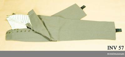 Långbyxor m/1923, Långbyxor m/1923 för general vid Generalitetet : Av gråbrungrön diagonal. Foder i livet av beige och brun  randigt siden. Två sidofickor, en bakficka. Spännslejf i ryggen. Resårhällor nedtill. Sju knappar i gylfen. Har tillhört Gustav VI Adolf (1882-1973).