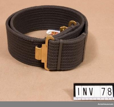 Livrem m/1952, Livrem m/1952 för Generalitetet : Samhörande nr är 1-119 (70-78, 119). Livrem m/1952: Av grå textil, bomull. Häktas fast med gulmetallkrokar. Har tillhört Gustav VI Adolf (1882-1973).