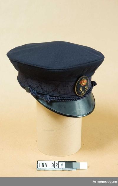 Skärmmössa m/1948, Skärmmössa m/1948 för amiral vid KSSS : Sydd i blått kläde med skärm av svartlackerat läder. Mössan är försedd med ståndare, svettrem, svart skärm, svart mössband samt två uniformsknappar av storlek 3, KSSS. KSSS galon runt ståndaren. KSSS mössmärke i svart, rött och guld, placerat mitt fram. Svart sidenfoder.