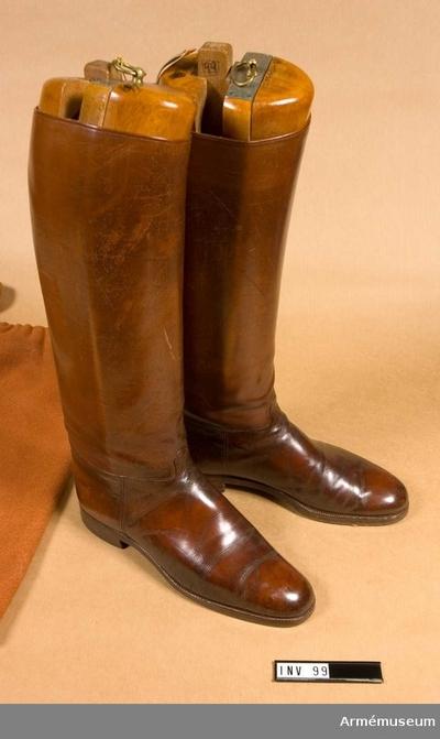 Ridstövel,  : Ridstövlar av brunt läder med randsydd lädersula och gummiklack. Storlek 44. Med tillhörande skoblock av fernissat trä, samt förvaringspåse i flanell.