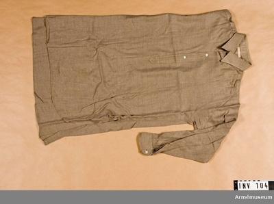 Skjorta m/1939, Skjorta m/1939 för generalitet : Skjorta m/1939, Generalitet. Skjorta av gråbrungrönt ylle. 390 mm långt sprund framtill som knäppes med tre pärlemorknappar. Skjortan har dubbelvikt krage med rundade hörn. Långa ärmar med manschett som knäppes med vit pärlemorknapp.  Samhörande gåvor AM.000001 - AM.000119.