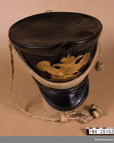 Tschakå m/1812, Tschakå m/1812 för manskap vid Preobrazhensky regement, Ryssland : Grupp C I. Ur uniform för manskap vid Livgardets Preobraschenskja  regementets 1:a regemente av 1:a gardesinfanteridivisionen: 1820-40.Tschakå (kiver) av svart kläde och svartlackerat läder. Övre delen har rund, rak botten. Skillnaden mellan diametern på övre och nedre delen är 111 mm. På framsidan finns en hållare för plym. Banderoll av vita garn snören med två tofsar. Foder av grovt, brunt läder. Hakrem av mässingsplåt. Skärm av lackerat läder. Vapenplåt på tschakåns främre del av mässing. En dubbelörn med S:t Göran bild finns ingraverad. LITT  F von Stein, Geschichte des russischen Heeres, Hannover 1885, sida 336: Denna tschakot infördes i ryska armén  26 september 1817. B Söderholm Livgardets 2. artilleribrigads historia, S Petersburg, 1898, sida 80 f: På gardets Tschakot fanns vapen och på dubbelörnen alltid en S:t Göransbild. Fig. sida 80 visar denna tschakot. Krigsenziklopedi, S Petersburg, 1912, del VII, sida 259: Vapenplåten på denna tschakå infördes vid ryska gardet år 1808.