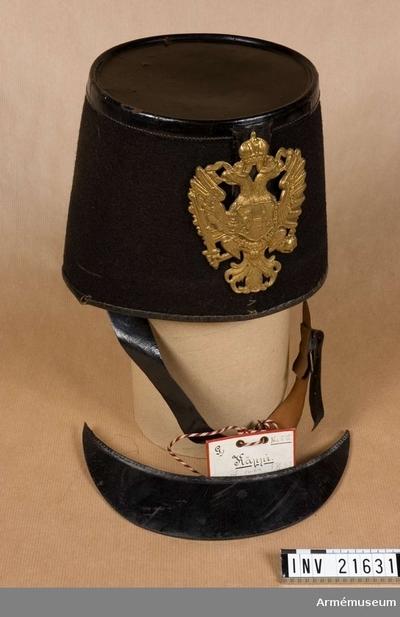 Käppi, Käppi för menig vid infanteriet, Österrike : Grupp C I. Klädd med svart kläde och botten med lack. På framsidan finns en läderficka för kokard och plym. Foder av lärft. Hakremmar av svart läder, med mässingsspännen. Vapenplåt av mässing med Österrikes vapen - dubbel örn och sköld.