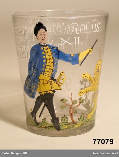 Bägare: Montertext i Dukade bordBägare av glas med emaljmålad bild av Karl XII samt hyllningsdikt på tyska till denne. 1700-talets början.Karl  XIIKunglighetUniform