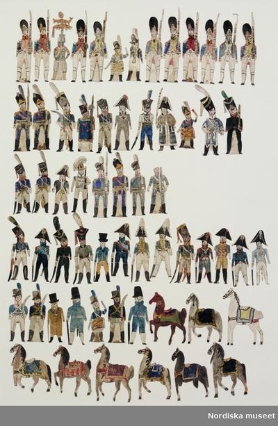 PappersdockaSoldatInventering Sesam 1996-1999: H 6-8 cm Papperssoldater tillverkade av spelkort och handkolorerade. Föreställande soldater, officerarere (52 st) och hästar (9.st). Vissa har stöd av papper mellan benen så att de kan stå. På baksidan av officerarna står det olika namn handskrivet, på soldater endast nummer. De är iklädda olika uniformer med olika sorters huvudbonader, de flesta med kort frackjacka och, höga stövlar och vapen av olika slag. Hästarna har sadeltäcken. Ur bilaga