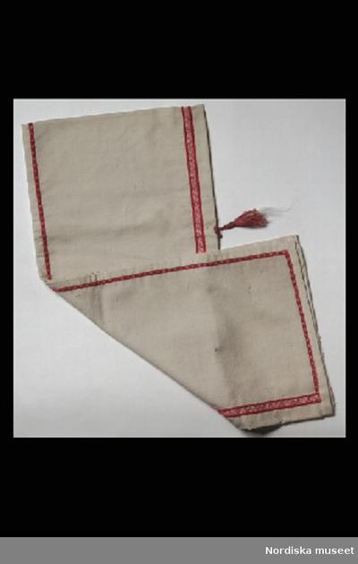 SchalBajadéreDockschalInventering Sesam 1996-1999: B 105 cm Docksjal, s.k. bayad¿re, viras runt huvudet och ner på axlarna, av vitt ylle, dekorerad med rött sidenband och en brun silketofs baktill. Helena Carlsson 1997