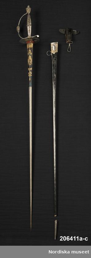 StudentvärjaVärja med balja och fäste.   Värjans blad är mot fästet blånat och med förgyllda motiv i klassicistisk stil. På ena sidan ornament som löper av sammansatta soltecken och mot fäste en tvärgående slinga i keltisk/fornnordisk stil. Fästet av sen 1700-tals modell med dekoration av fasettslipade stålkulor.   Balja av trä klädd med svart läder och med ornamenterat mässingsbläck. Enligt uppgift skall bläcket vara stucket med texten Kolb á parus.  Fästet för att bära värjan med fjäderhake som skall fästas i en ögla på baljan.   Per Larsson 2013-03-14Kolb á parus