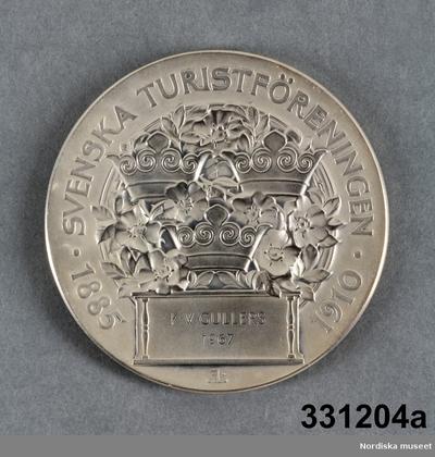 Medalja) Medalj b) Etui c) Diplom  a) Medalj av silver, rund form, på åtsidan ung man och kvinna i relief och text
